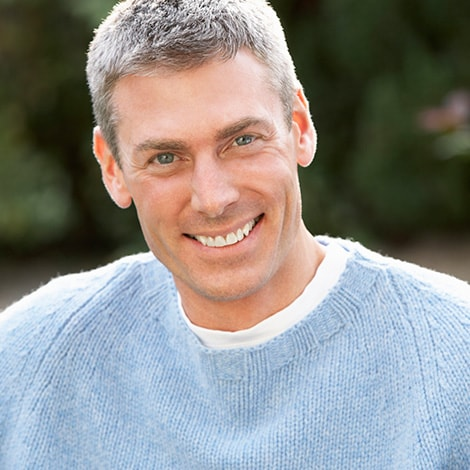 A mature man wearing a gray sweater