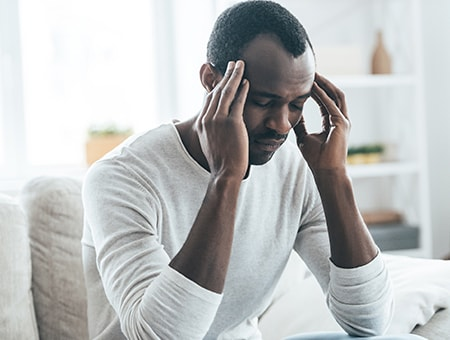 A middle-aged man sitting on a sofa suffering from a headache