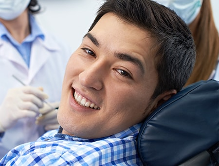 A young man sitting in a dental chair while waiting for his dental check-up
