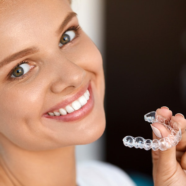 A young woman smiling while holding Invisalign clear aligners