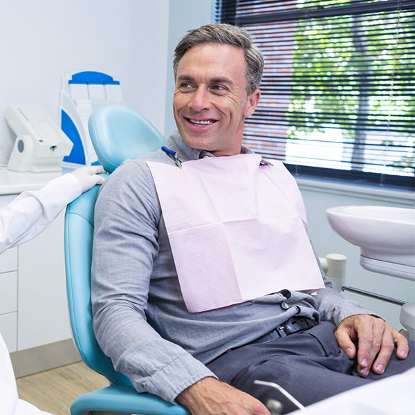 An older man sitting in a dental chair while smiling with his hands in his lap