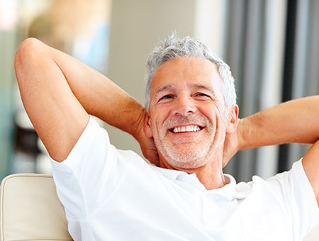 An older man smiling as he sits on a sofa with his hands behind his neck
