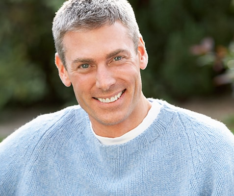An older man smiling while wearing a gray sweater