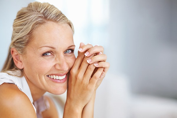 A mature woman smiling as she leans forward