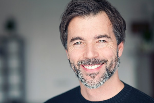 A mature man with a beard wearing a black sweater