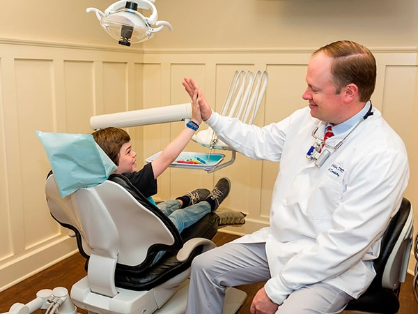 Dr. Collier giving a young patient a high-five after his dental treatment