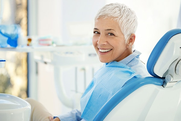 A mature woman sitting in a dental chair