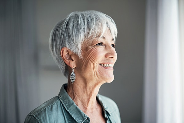 An older woman smiling while standing off to the side