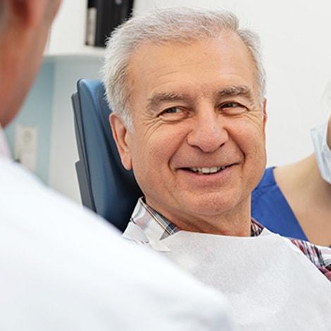 A mature man smiling in a dental chair
