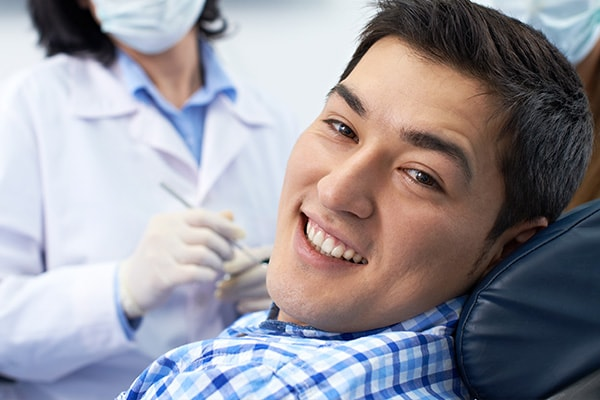 A young man wearing a plaid shirt sitting in a dental chair