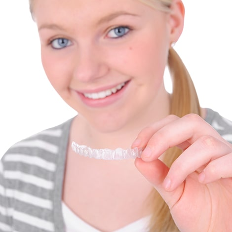 A blonde teenage girl holding Invisalign clear aligners