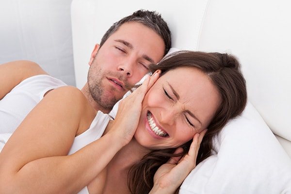 A woman who cannot sleep due to her husband snoring next to her in bed