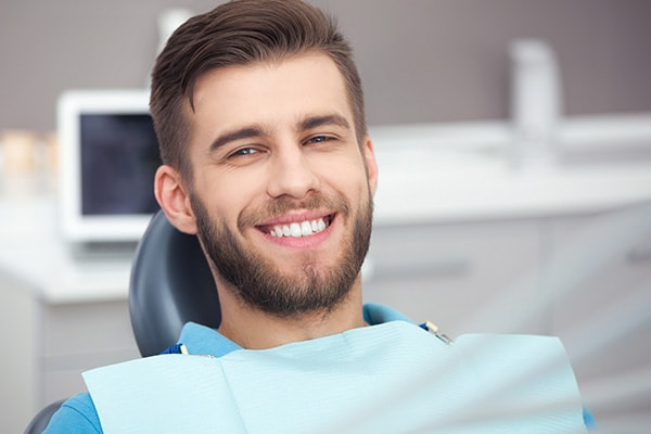 A young man with a beard waiting for an oral surgery in a dental chair
