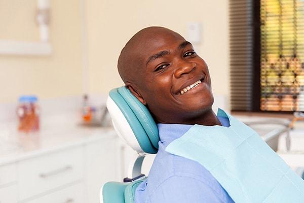 A man sitting in a dental chair with a blue bib