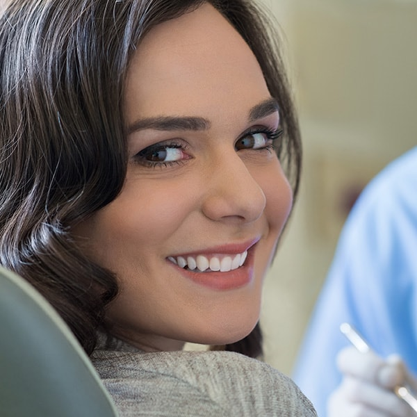 A young woman smiling with her new porcelain veneers