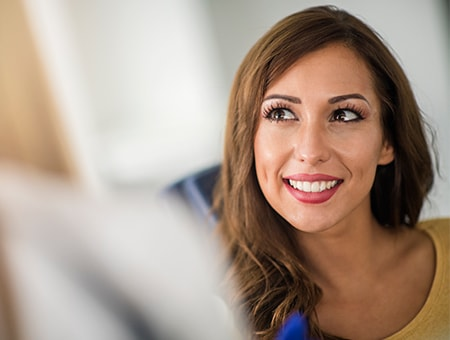 A young woman smiling up at her dentist from the dental chair
