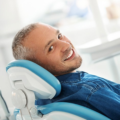 A mature man lying in a dental chair while smiling