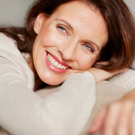 A mature woman smiling as she lies down on a sofa